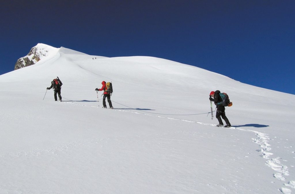 3 people climbing a snowy moutain