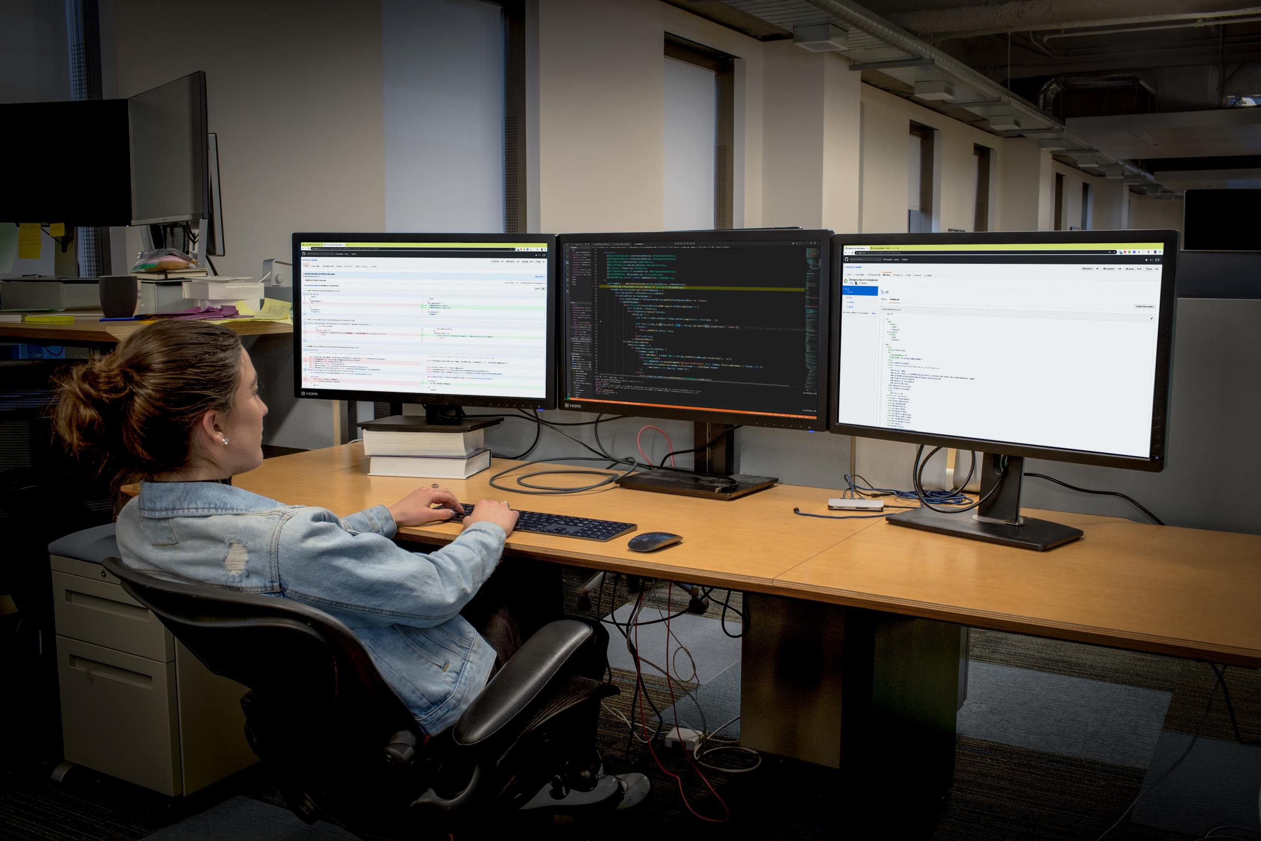 A man on his headset, having a call on Microsoft Teams and working on 2 screens
